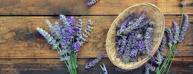 Ramo de flores de lavanda ao lado de uma pequena cesta cheia de pétalas de fundo de madeira