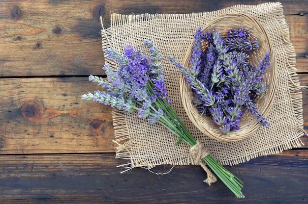Ramo de flores de lavanda ao lado de uma pequena cesta cheia de pétalas em têxteis e fundo de madeira