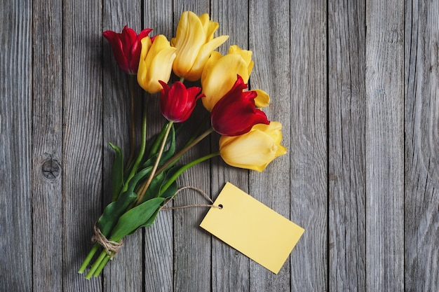 Ramo de flores de tulipa com cartão de nome em branco em fundo de madeira, espaço de cópia