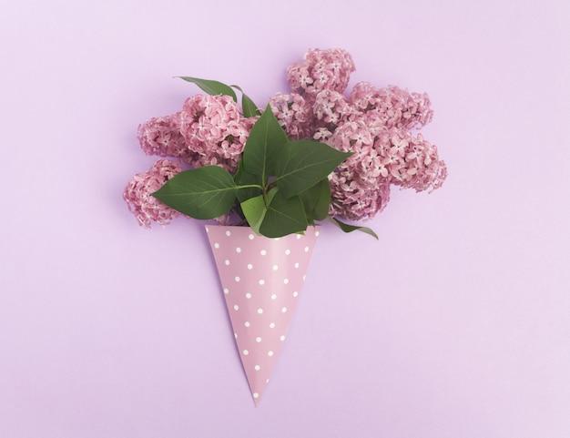 Ramo de flores lilás em cone de papel no fundo roxo de cima, plano