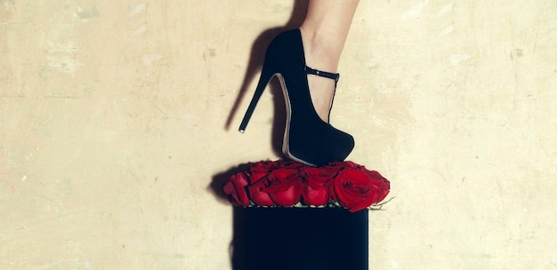 Ramo de flores naturais frescas de salto alto feminino em rosas vermelhas em caixa de presente preta