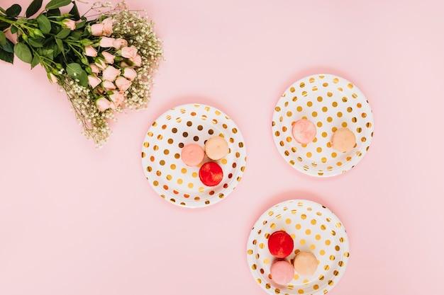Ramo de flores perto de pratos com sobremesa