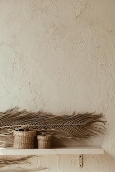 Ramo de folha de palmeira seca e caixões de vime na parede de concreto.