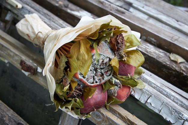 Ramo de frutas podres e flores murchas