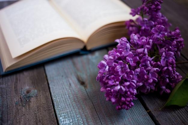 Ramo de livro lilás e aberto em um fundo de madeira