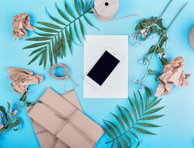 Ramo de palmeira, caixas de presente, smartphone branco e corda de juta hank sobre um fundo azul, estilo verão