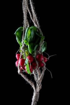 Ramo de rabanetes com folhas entrelaçadas em uma corda que os sustenta