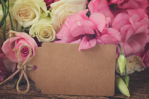 Ramo de rosas frescas brancas e rosa e flores de eustoma com nota de papel vazio, em tons retrô