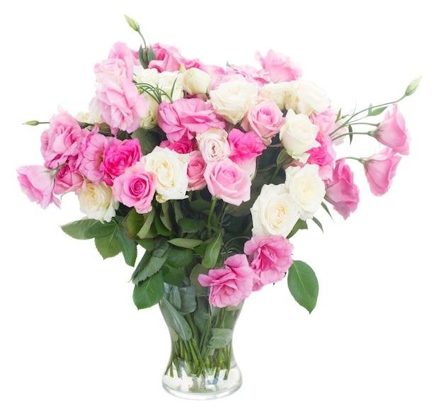 Ramo de rosas frescas brancas e rosa e flores de eustoma em um vaso de vidro isolado