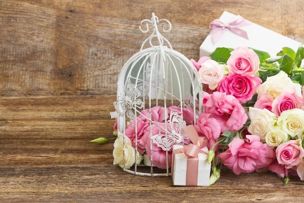 Ramo de rosas frescas cor de rosa e brancas e flores eustoma com caixa de presente em fundo de madeira