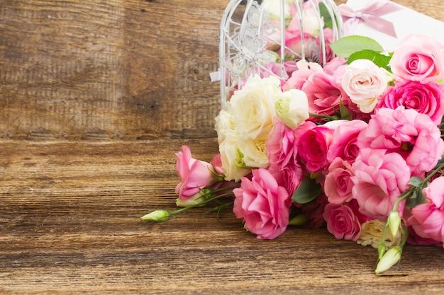 Ramo de rosas frescas cor de rosa e brancas e flores eustoma em fundo de madeira