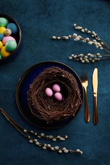 Ramo de salgueiro florescendo, ovos de páscoa no ninho e talheres. flor de árvore da primavera e comida pascal, decoração floral fresca para a celebração do feriado, símbolo do evento