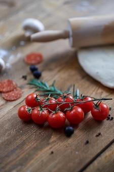 Ramo de tomate cereja deitado na mesa. ingredientes diferentes sem foco