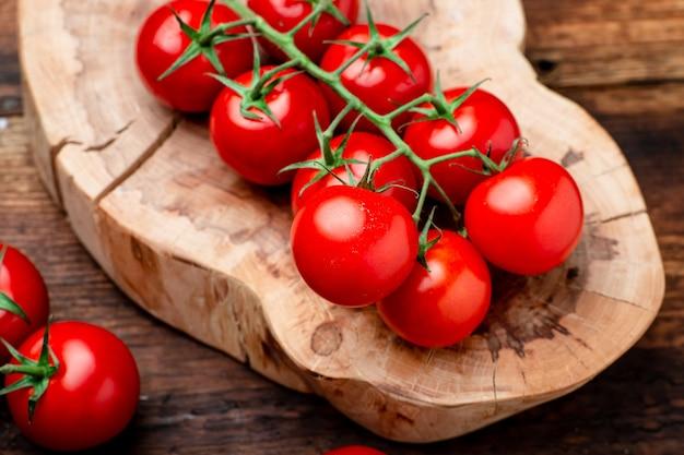 Ramo de tomate cereja fresco em um fundo de madeira marrom.
