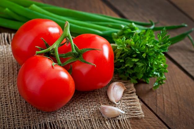 Ramo de tomate fresco na mesa de madeira