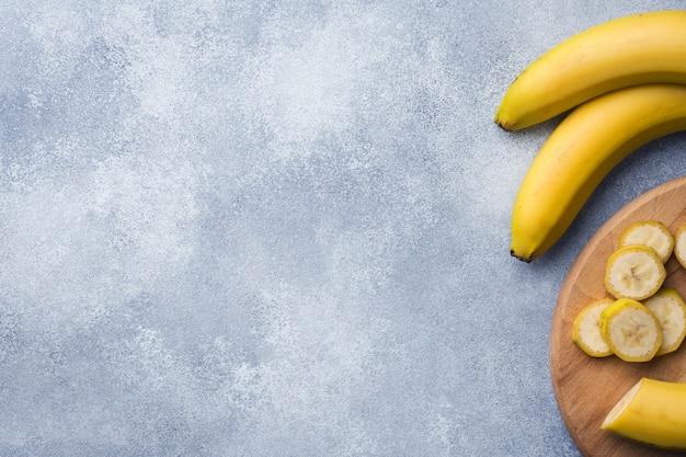 Ramo de três bananas em um plano de fundo texturizado,