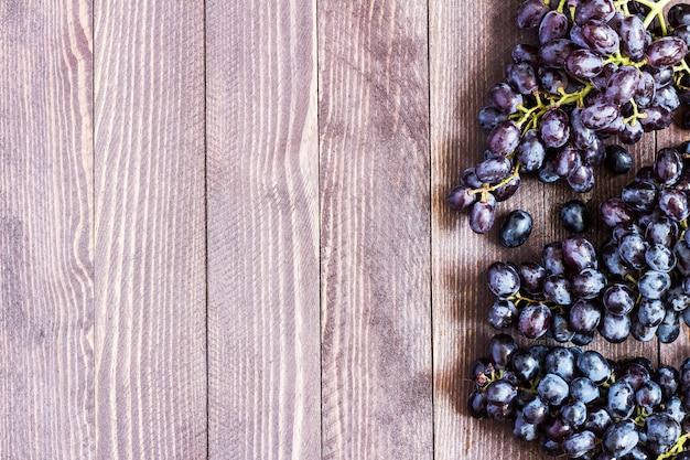 Ramo de uva preta em madeira escura