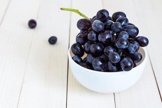 Ramo de uva preta na tigela em madeira branca