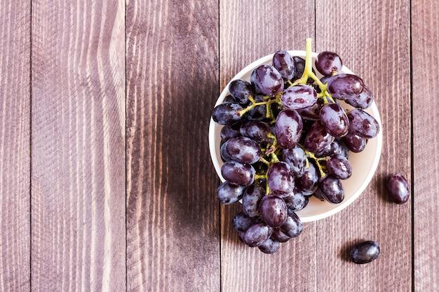 Ramo de uva preto na tigela em madeira escura