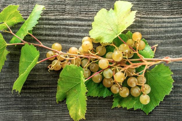 Ramo de uvas em uma mesa de madeira