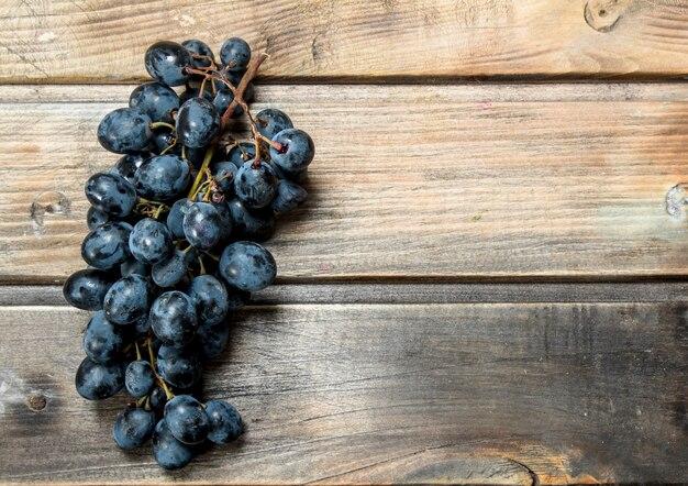 Ramo de uvas pretas na mesa rústica.