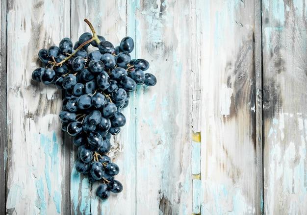 Ramo de uvas pretas. sobre um fundo rústico.