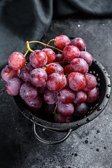 Ramo de uvas vermelhas suculentas em uma peneira. fundo preto.