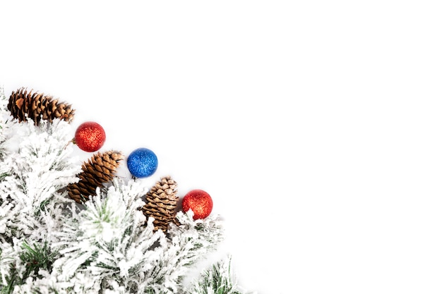 Ramo decorativo spruce coberto de neve com cones e bolas de ano novo em um fundo branco. espaço para texto.