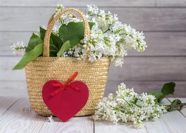 Ramo lilás em uma cesta e um coração com fita