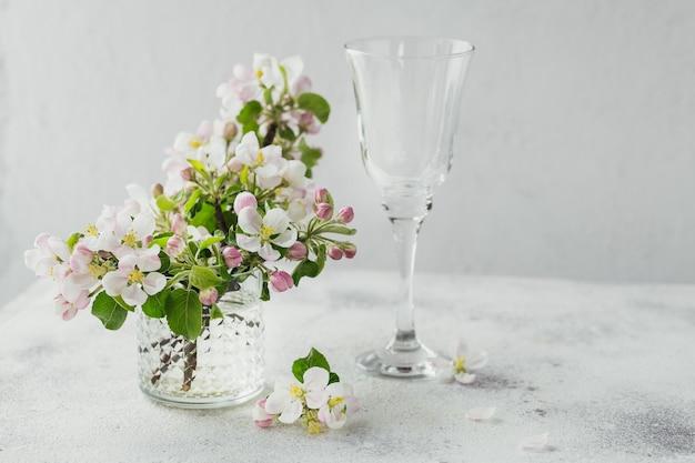 Ramos com flores de maçã branca em um vidro transparente em uma superfície cinza
