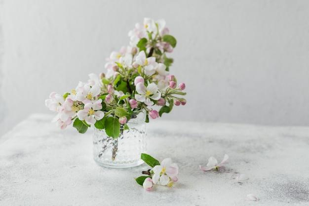Ramos com flores de maçã branca em um vidro transparente sobre um fundo cinza. natureza morta, cartão de páscoa