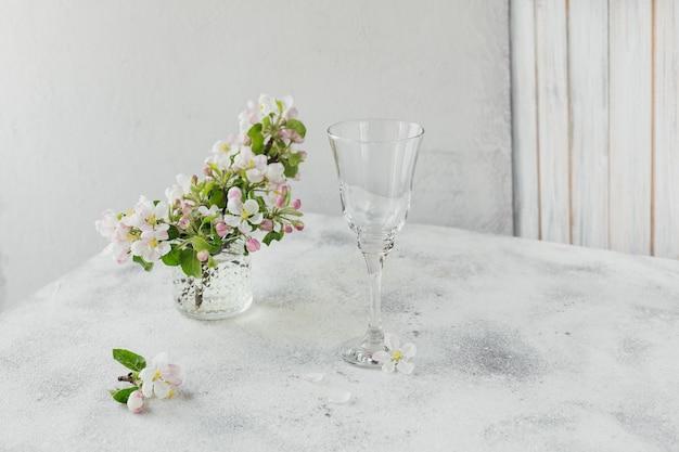 Ramos com flores de maçã branca em vidro transparente