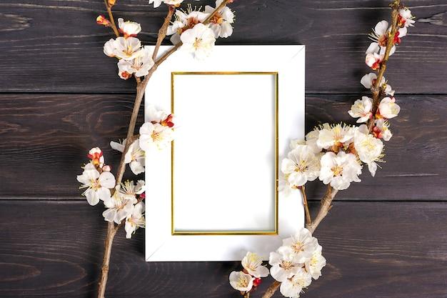 Ramos da árvore de damasco com moldura de flores, branco sobre fundo de madeira.