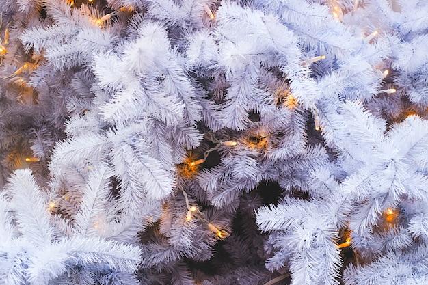 Ramos de abeto branco brancos de uma árvore de natal artificial com luzes amarelas. espaço de cópia de segundo plano.