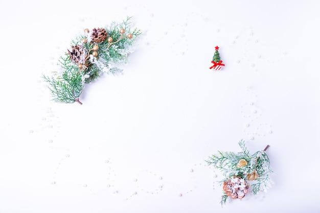 Ramos de abeto com cones, uma árvore de natal em miniatura e contas de pérolas em um fundo branco. colocação plana de ano novo. copie o espaço para o texto.