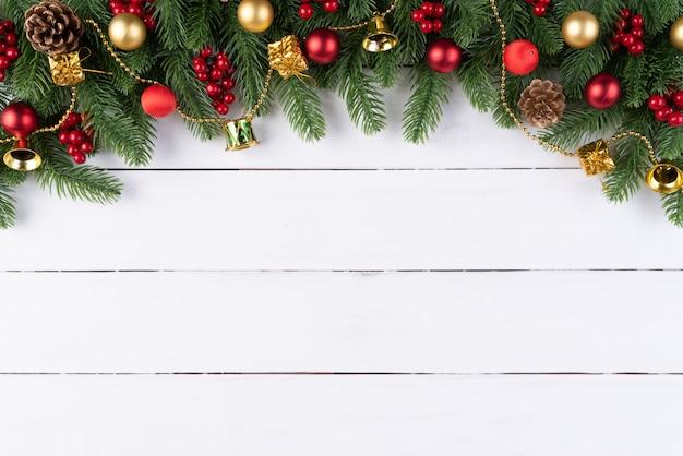 Ramos de abeto de natal, pinhas, bagas vermelhas em fundo de madeira.