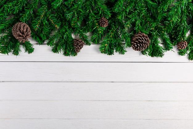 Ramos de abeto e pinhas na placa de madeira branca