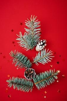 Ramos de abeto em forma de árvore de natal com confetes festivos em fundo vermelho
