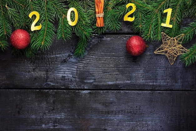 Ramos de abeto estrela de natal e bola de natal com a inscrição na decoração de madeira preta para o ...