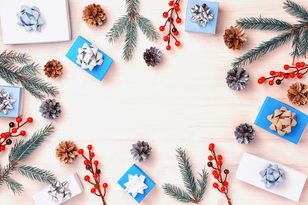 Ramos de abeto, frutas vermelhas, pequenas caixas e cones encontram-se em um círculo. presentes decorados com laços em prata e ouro. sobre um fundo claro de madeira, copie o espaço.