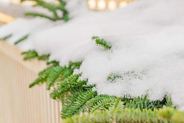 Ramos de abeto vermelho cobertos de neve por cima da cerca de madeira.