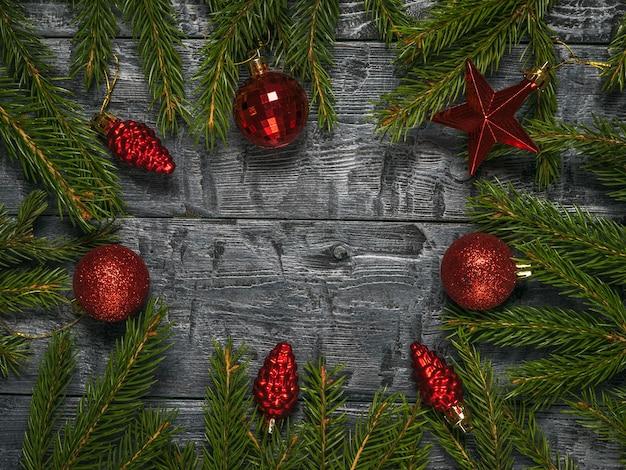 Ramos de abeto vermelho com enfeites de vidro vermelho de natal em um fundo de madeira.