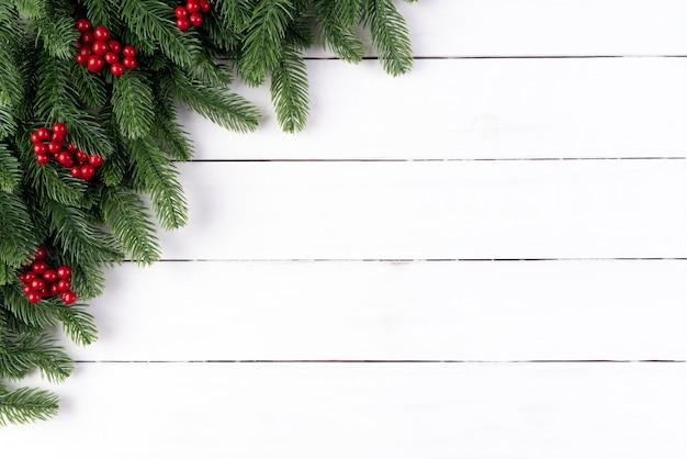 Ramos de abeto vermelho de natal e bagas vermelhas em fundo de madeira.
