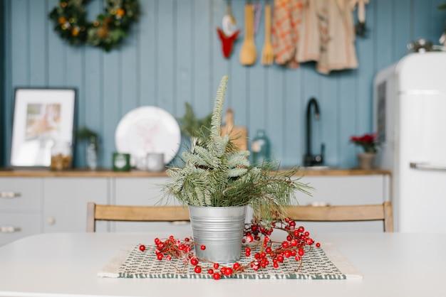 Ramos de abeto vermelho frescos ou peônias ou pinheiros em um balde de metal, vaso na mesa da cozinha na decoração para cozinha de natal e ano novo
