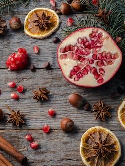 Ramos de abeto vermelho romã anis estrelado, canela e especiarias de inverno na madeira