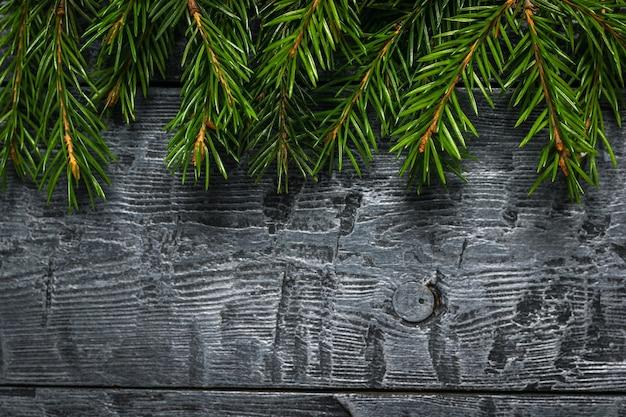Ramos de abeto vermelho verdes sobre um fundo preto de madeira.