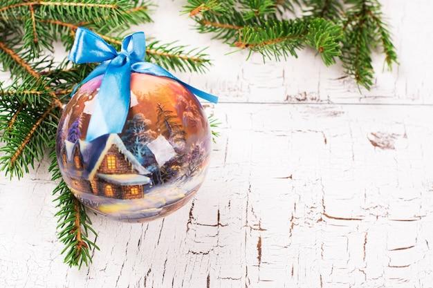 Ramos de árvore bonitos do abeto da sagacidade da bola da árvore de abeto do natal sobre o fundo de madeira branco.