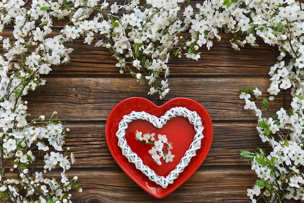 Ramos de árvore de florescência brancos da cereja com forma vermelha do coração do prato.