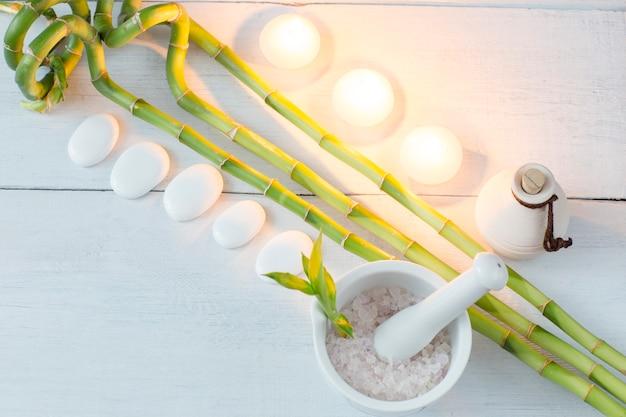 Ramos de bambu, óleo, velas, sal do mar e pedras brancas (spa) em uma mesa de madeira branca