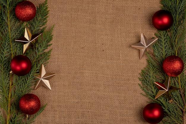 Ramos de carvalho verde com bolas vermelhas de natal e estrelas douradas nos dois lados.